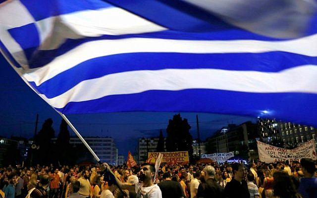 A demonstrator waves a Greek flag during an anti-austerity rally in central Athens, Friday, July 10, 2015. (AP Photo/Petros Karadjias)