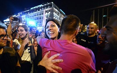 Greek parliament's president and Syriza party member, Zoe Kostantopoulou  (C)  embraces a 'NO' supporter , as she joins the celebrations in  front of the parliament latein Athens on July 5, 2015. Greece's Prime Minister Alexis Tsipras said that the 'No' victory in the country's bailout referendum did not mean Athens was headed for a so-called Grexit. AFP PHOTO / Louisa Gouliamaki