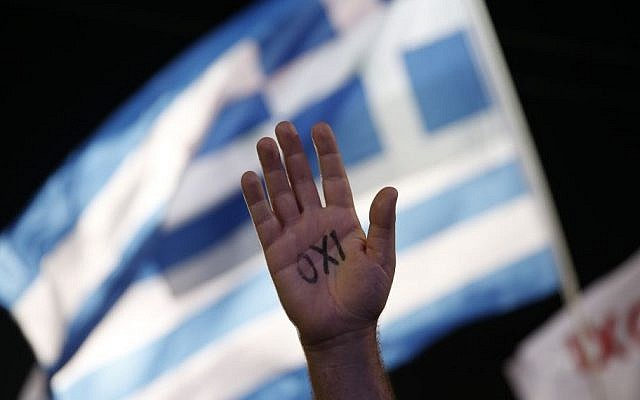 A demonstrator raises his hand with the word ''No'' written on it as a Greek flag waves behind during a rally organized by supporters of the No vote in Athens. July 3, 2015 (AP /Petros Giannakouris, File)