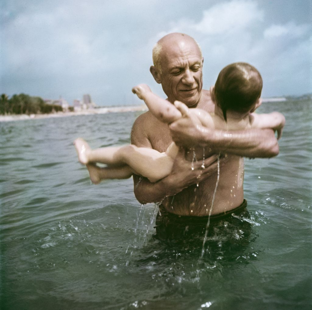 The 1948 photo by Robert Capa provided by the International Center of Photography/Magnum Photos shows Pablo Picasso playing in the water with his son Claude in Vallauris, France. (Robert Capa/International Center of Photography/Magnum Photos via AP)