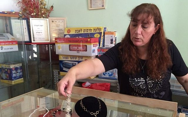 Vered Tartiks shows off some of the jewelry she makes. Because the bank seized her car due to debts, she cannot travel to craft fairs to sell the jewelry.  (Luke Tress/Times of Israel)