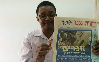 Dr. Anbessa Teferra, a professor of Semitic languages at Tel Aviv University, with a copy of Yedioth Negat, an Amharic newspaper. (Ilan Ben Zion/Times of Israel staff)