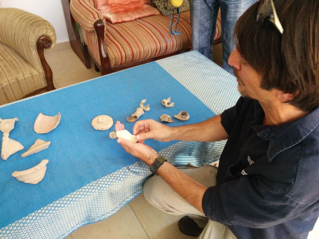 IAA archaeologist Amit Reem examines remains of ceramic and stone vessels found in a first century Jewish ritual bath in the Shimshoni home in Ein Karem, on July 1, 2015. (Ilan Ben Zion/Times of Israel staff)