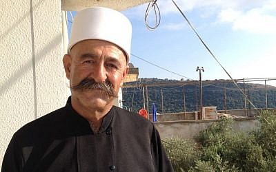 Sheikh Hayel Sharaf stands outside his home in Ein Kinya in the Israeli Golan Heights, July 8, 2015 (Elhanan Miller/Times of Israel)