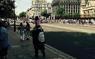 An unidentified man is spotted by tourists walking around London wrapped in an Islamic State flag, carrying a child also waving the flag, July 2015. (Twitter)