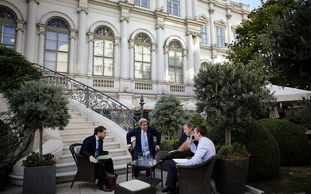 US Secretary of State John Kerry, center, and State Department Chief of Staff Jon Finer, left, meet with other members of the US delegation at the garden of the Palais Coburg hotel where the Iran nuclear talks meetings are being held in Vienna, Austria, Friday July 10, 2015. (Carlos Barria/Pool via AP)
