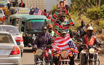 People on motor bikes celebrate American President Barack Obama's visit to Kenya by holding up a photo, center top, of the president and First Lady Michelle Obama in Kisumu, Kenya, Saturday, July 25, 2015. (AP)