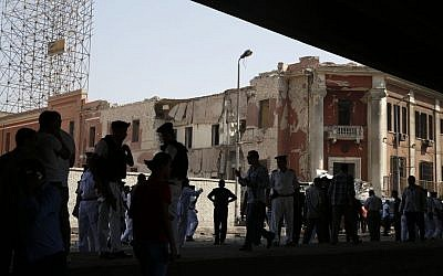 Egyptian policemen stand at the base of the crumbled facade of the Italian consulate following a blast that killed at least one person in Cairo, Egypt, Saturday, July 11, 2015 (Hassan Ammar/AP)