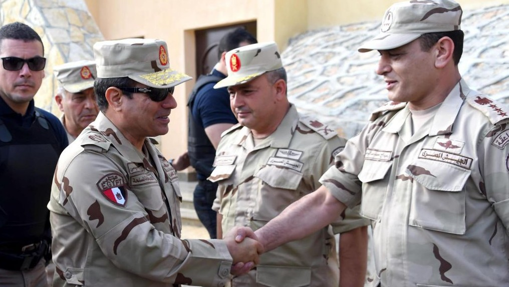 In this picture provided by the office of the Egyptian Presidency, Egyptian President Abdel-Fattah el-Sissi, second left, greets members of the Egyptian armed forces in Northern Sinai, Egypt, Saturday, July 4, 2015.(Egyptian Presidency /Mohammed Abdel-Muati via AP)