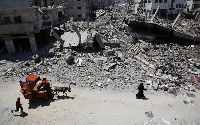 In this August 1, 2014, file photo, Palestinians carry their belongings through the heavily bombed Gaza City neighborhood of Shujaiyah, close to the Israeli border. (AP/Hatem Moussa)
