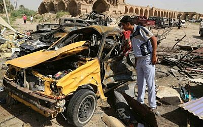 A civilian inspects the aftermath of a suicide car bombing claimed by Islamic State at a busy market in Khan Bani Saad in the Diyala province, about 20 miles (30 kilometers) northeast of Baghdad, Iraq, July 18, 2015. (AP/Karim Kadim)