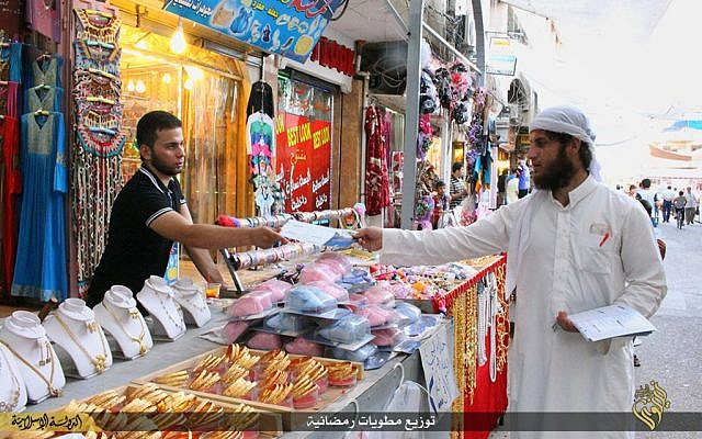In this Tuesday, June 16, 2015 photo provided by a website of the Islamic State group, an IS member, right, distributes pamphlets about fasting before the Muslim holy month of Ramadan in Mosul, northern Iraq.  (Islamic State militant via AP)