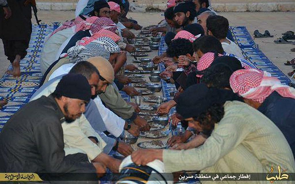In this photo provided by a website of the Islamic State group, Muslims eat their meals distributed by the IS group as they break their fast during the holy month of Ramadan in the northern Syrian province of Aleppo, June 20, 2015. (Islamic State militant via AP)