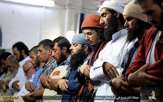 "In this Saturday, June 20, 2015 photo provided by a website of the Islamic State group, Muslims perform ""Taraweeh,"" a special night's prayers during the Muslim holy month of Ramadan, in the eastern city of Deir el-Zour, Syria. (Islamic State militant via AP)"