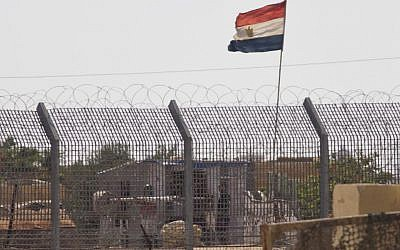 Illustrative: An Egyptian military officer keeps watch at a post in Egypt's northern Sinai Peninsula, as seen from the Israel-Egypt border, in the village of Kerem Shalom in southern Israel, July 1, 2015. (AP/Ariel Schalit)
