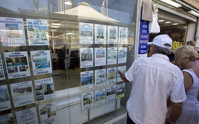 A couple looks at real estate ads in the coastal city of Netanya, July 29, 2015. (AP Photo/Sebastian Scheiner)