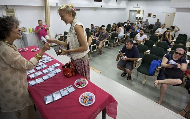 In this photo taken Wednesday, July 29, 2015, a French immigrant to Israel receives her Israeli ID during a ceremony in the coastal city of Netanya central Israel. (AP Photo/Sebastian Scheiner)