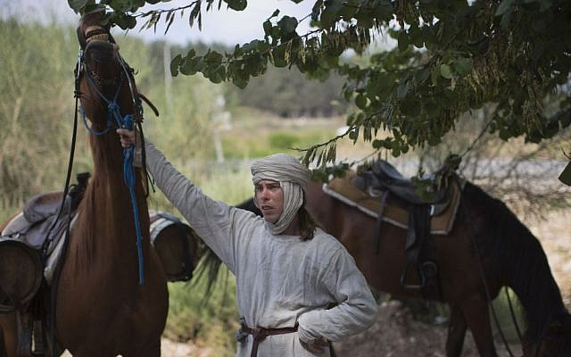 Israeli and Russian members of knight clubs get on their horses before marching to the reenactment of the Battle of Hattin July 3, 2015. (AP/Oded Balilty)