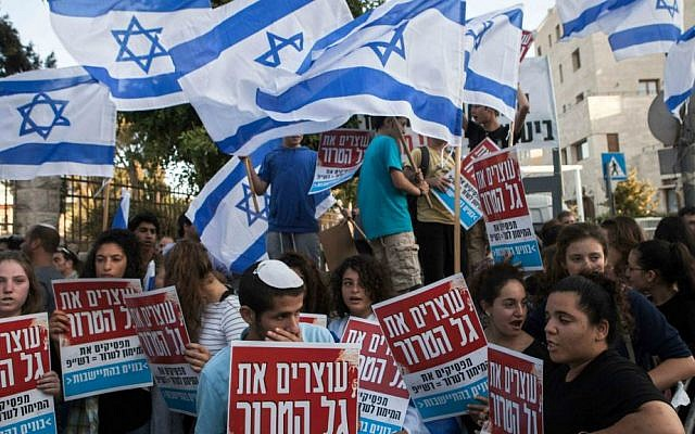 Israelis hold signs and wave flags during a demonstration outside the prime minister's residence in Jerusalem on Wednesday, July 1, 2015, calling on Prime Minister Benjamin Netanyahu to act against recent Palestinian attacks against Israelis. (AP Photo/Dan Balilty)