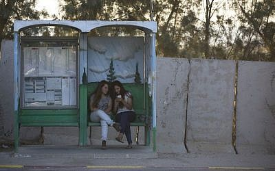 Israeli girls wait for transportation in a bus stop protected with concrete blocks near the southern Israeli town of Sderot, next to the Israel-Gaza border, June 30, 2015. (AP Photo/Oded Balilty)