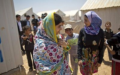 Nobel Peace Prize laureate Malala Yousafzai, 18 (left), walks with Mezon al-Melihan, a 17-year-old refugee from the southern Syrian town of Deraa, during Malala's visit to the Azraq refugee camp in Jordan, July 13, 2015. (AP/Muhammed Muheisen)