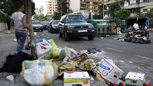 A Syrian boy watches vehicles driving past dumpsters and a pile of garbage in Beirut, Lebanon, Sunday, July 26, 2015 (AP Photo/Hassan Ammar)
