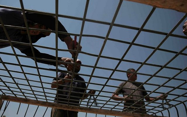 Palestinian workers prepare rebar to rebuild a house which was destroyed during last summer's war between Israel and Hamas, as the long-awaited reconstruction began in the Shejaiya neighborhood of eastern Gaza City on Thursday, July 23, 2015. (AP Photo/Khalil Hamra)