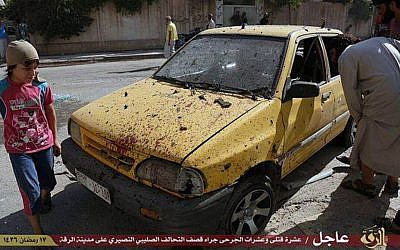 This Saturday, July, 4, 2015 photo provided by a website of the Islamic State group, shows people inspecting a car purportedly damaged by US-led airstrikes on Raqqa, Syria. (Islamic State militant website via AP)