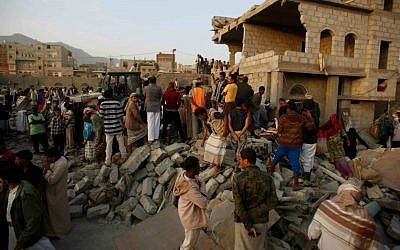 People search for survivors under the rubble of houses destroyed by Saudi airstrikes in Sanaa, Yemen, Monday, July 13, 2015. (AP Photo/Hani Mohammed)