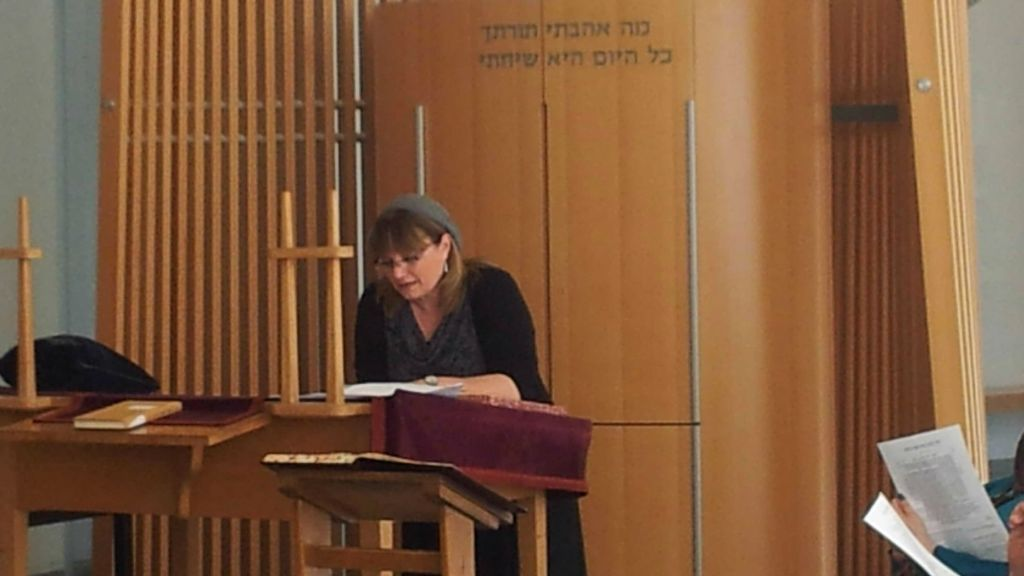 Rabbinical student Nathalie Lastreger reads from the altar at the Schechter Rabbinical Seminary. (courtesy)