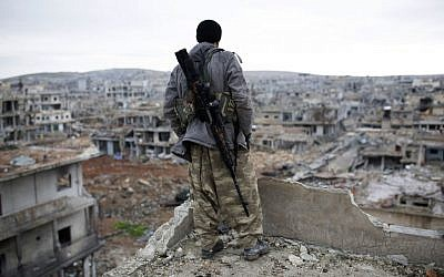 A Syrian Kurdish sniper looks at the rubble in the Syrian city of Ain al-Arab, also known as Kobani, Jan. 30, 2015 (AP, File)