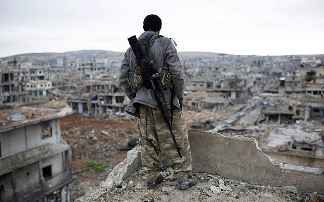 A Syrian Kurdish sniper looks at the rubble in the Syrian city of Ain al-Arab, also known as Kobani, Jan. 30, 2015. (AP, File)