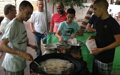 Vendors selling falafel at the nightly Ramadan market in Kfar Qasim. (Ben Sales)