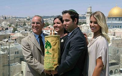 From left: Stuart, Evie, Jake, and Paige Steinberg on July 12 with a Torah scroll, adorned with Golani colors and symbol, written in honor of Sgt. Max Steinberg (Luke Tress/ Times of Israel)