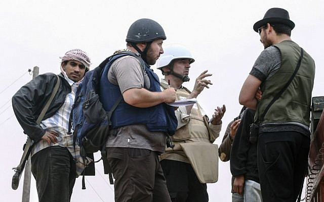 In this handout image made available by the photographer, American journalist Steven Sotloff, center with black helmet, talks to Libyan rebels on the Al Dafniya front line, about 15 miles from Misrata, Libya, June 2, 2011. Sotloff was beheaded in September 2014 nearly a year after being kidnapped in Syria. (Etienne de Malglaive via Getty Images/JTA)