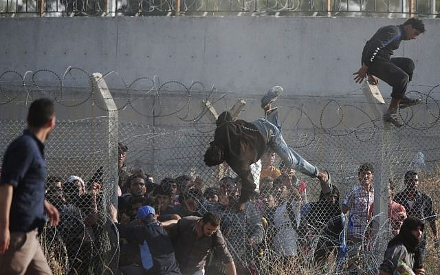 In this June 14, 2015, file photo, Syrian refugees cross into Turkey from Syria over and through a hole on the border fence in Akcakale, Sanliurfa province, southeastern Turkey. (AP Photo/Lefteris Pitarakis, File)