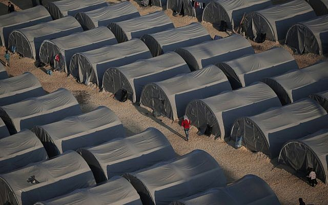 In this Oct, 17, 2014, file photo, Syrian Kurdish refugees who fled fighting in Kobani, Syria, go about at a refugee camp in Suruc, on the Turkey-Syria border. (AP Photo/Lefteris Pitarakis, File)