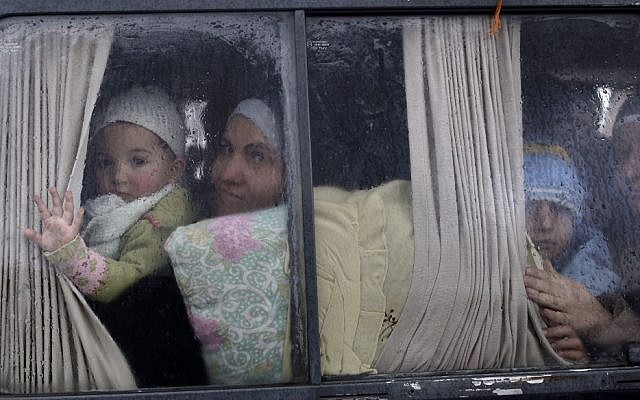In this Dec. 20, 2012, file photo, Syrian refugees, who fled their home in Idlib due to a government airstrike, look out of a vehicle's window just after crossing the border from Syria to Turkey in Cilvegozu, Turkey. (AP Photo/Muhammed Muheisen, File)