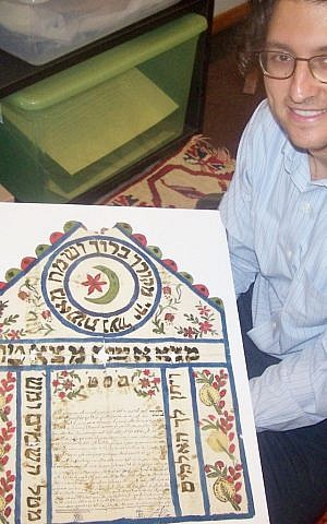 Prof. Devin Naar holds a Jewish wedding contract from Tekirdag, Turkey, 1919 that was donated by Rabbi Solomon Maimon. The inclusion in this document of the star and crescent, symbols of Islam and the Ottoman Empire, indicate the sense of belonging that Jews felt for the Ottoman Empire. (Janis Siegel/The Times of Israel)