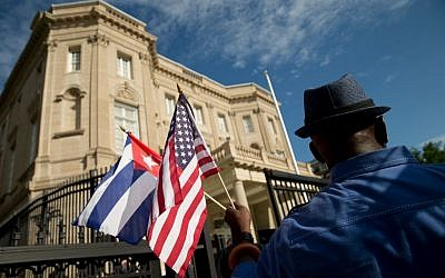 Edwardo Clark, a Cuban-American, holds an American flag and a Cuban flag as he celebrates outside the new Cuban embassy in Washington, Monday, July 20, 2015. (AP Photo/Andrew Harnik)