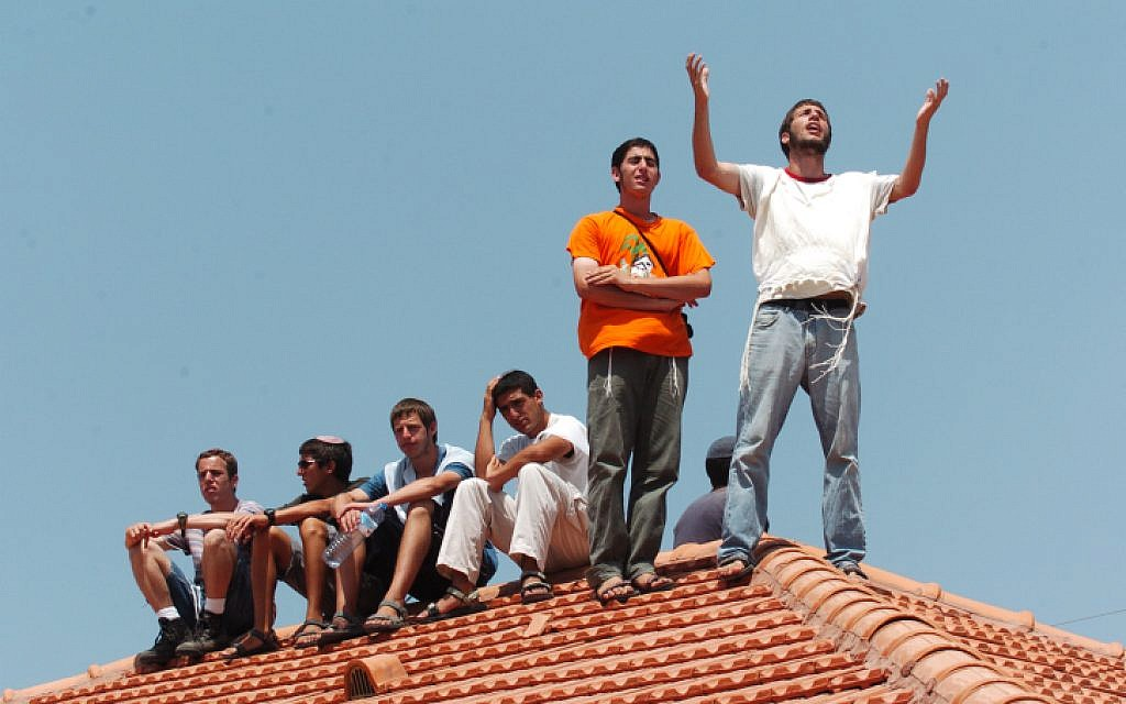 File: Young settlers cry and pray on the roof during the disengagement in Neve Dkalim on August 17, 2005. (Nati shohat Flash90)