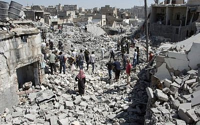 Syrians stand on the rubble of buildings after a missile fired by Syrian government forces hit a residential area in the Maghayir district in the old quarter of the northern Syrian city of Aleppo on July 21, 2015. (Photo by AFP Photo / Karam Al-Masri)