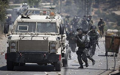 IDF soldiers clash with Palestinians after the funeral of Falah Abu Maria in the village of Beit Omar near the West Bank city of Hebron, Thursday, July 23, 2015.  (AP Photo/Majdi Mohammed)