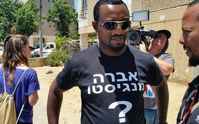 An activist with a T-shirt for Avraham Mengistu, who is currently believed to be held by Hamas in Gaza, outside his family's home in Ashkelon, July 9, 2015. (Twitter)