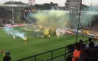 Smoke bombs and flares are thrown onto the pitch by fans of Beitar Jerusalem soccer club during an away match against Belgian team Sporting Charleroi on Thursday, July 16, 2015. (screenshot: Ynet)