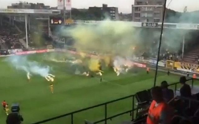 Smoke bombs and flares are thrown onto the pitch by fans of Beitar Jerusalem soccer club during an away match against Belgian team Sporting Charleroi on Thursday, July 16, 2015. (screenshot:Ynet)