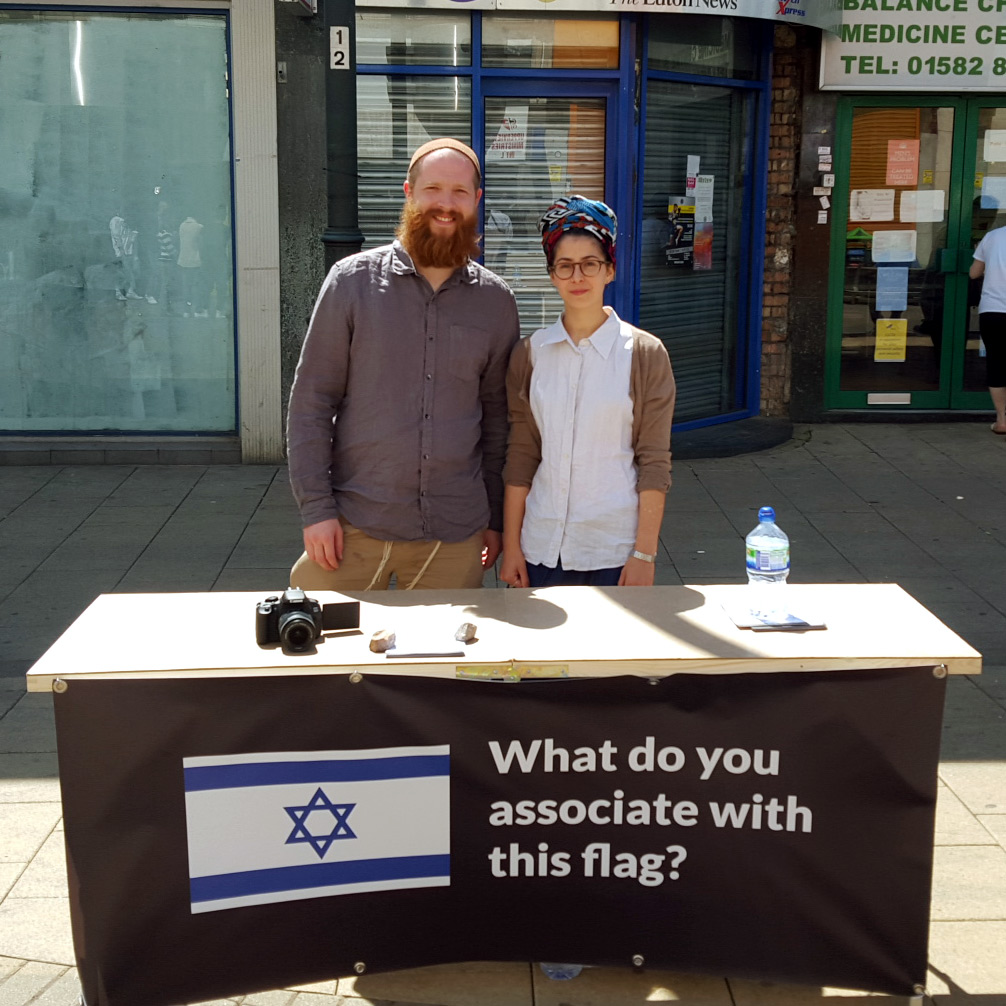 Joseph Cohen and wife Chloe at an information table. 'I was inspired by [Muslim] evangelism and ability to convert thousands of people to Islam in Britain using similar tactics. You can see their stalls on many street corners where with free material and well trained advocates they persuade large numbers of people to join Islam.' courtesy)