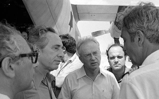 Rabin, center, with Peres, directly to Rabin's right, speaking with what looks like one of the Air France crew members, who bravely stuck with the Israeli hostages (Courtesy IDF Archive)