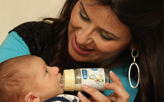 A mother feeds her two week old baby with milk substitute. (Nati Shohat/Flash90)