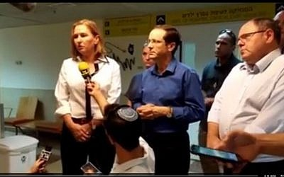 Zionist Union leaders Tzipi Livni and Isaac Herzog with former Yesha Council spokesperson Danny Dayan (R) speaking to the press at the Sheba hospital in Tel Hashomer on Friday, July 31 2015. The hospital is treating two members of the Dawabsha family after a firebomb on their home killed a baby and left three people with severe burns. (Screen capture, Facebook)